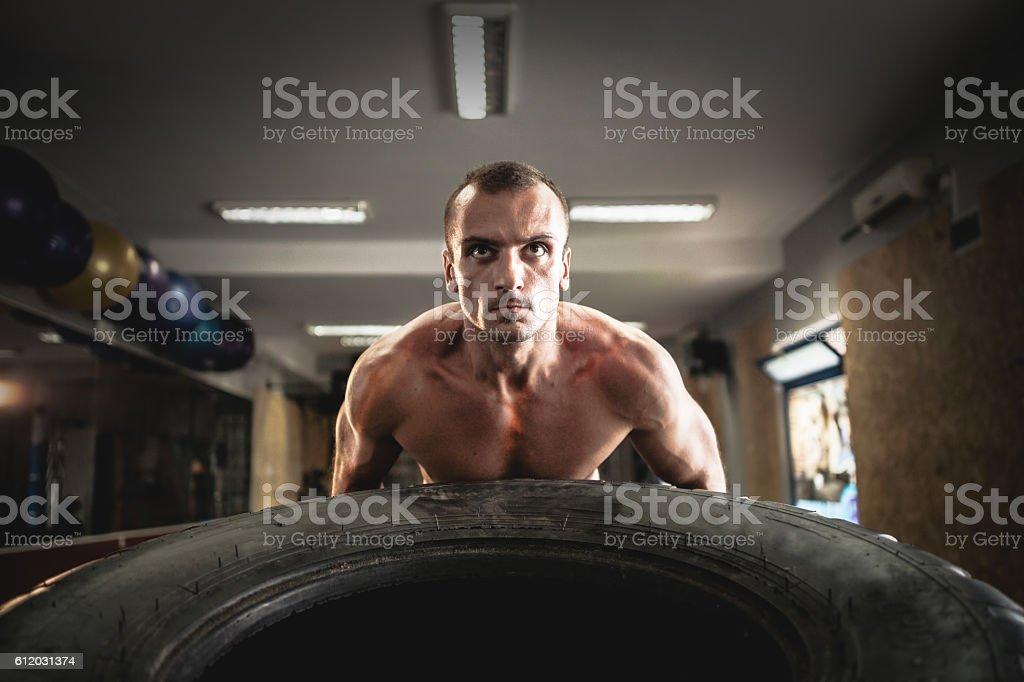 Man pushing tire in gym stock photo