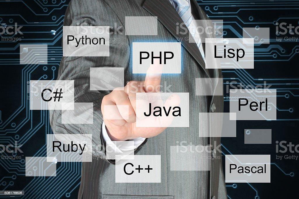 Man pushing virtual programming language button stock photo