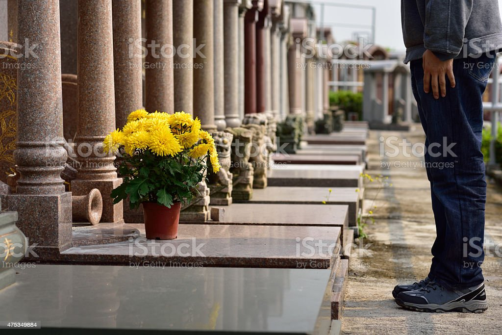 man put flower in front of tomb of ancestor stock photo