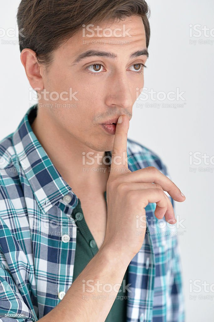 man puts finger on her lips stock photo