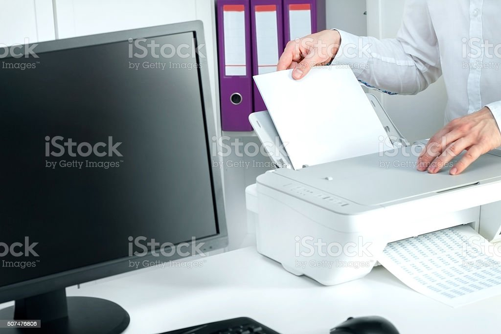 Man puts stack of paper into white printer stock photo