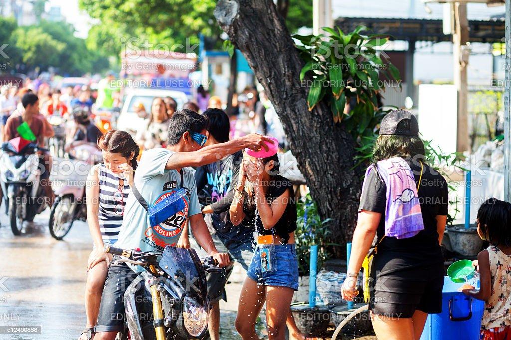 Man puts water on thai girl stock photo