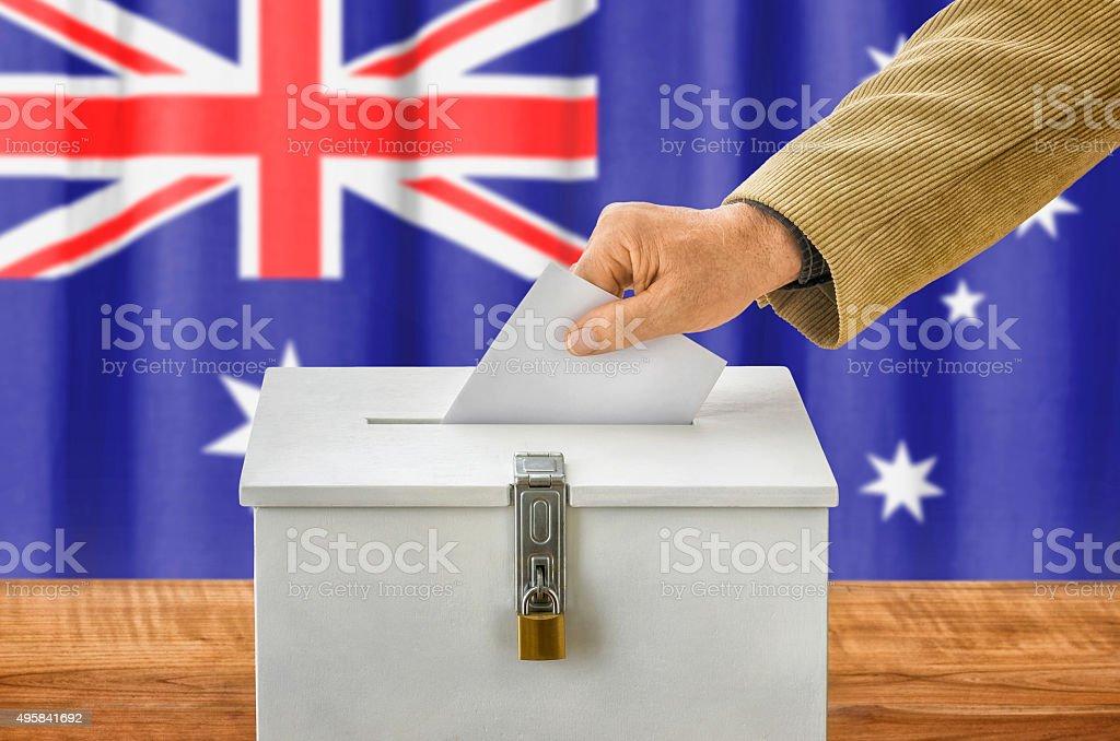 Man putting a ballot into a voting box - Australia stock photo