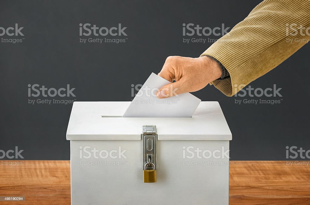 Man putting a ballot into a voting box stock photo