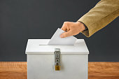 Man putting a ballot into a voting box