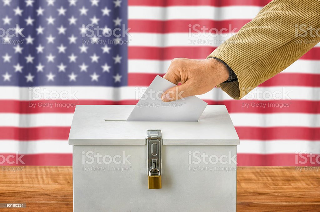 Man putting a ballot into a voting box - USA stock photo