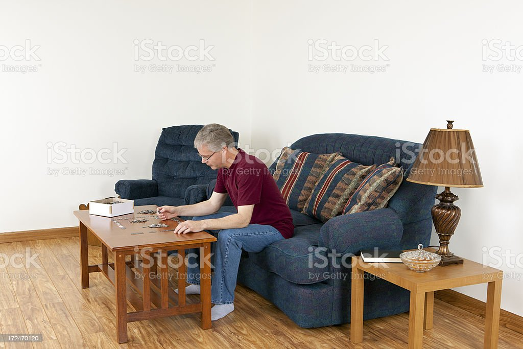 Man Putting a Puzzle Together stock photo