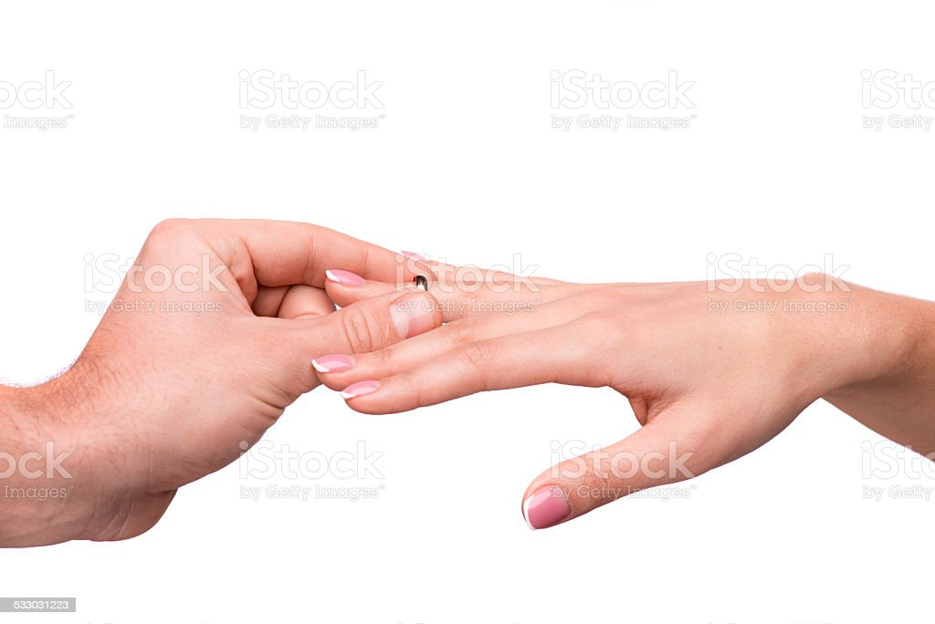 Man putting a wedding ring on her finger stock photo