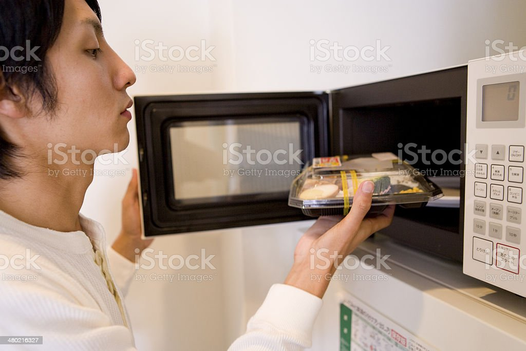 Man putting boxed lunch into microwave stock photo
