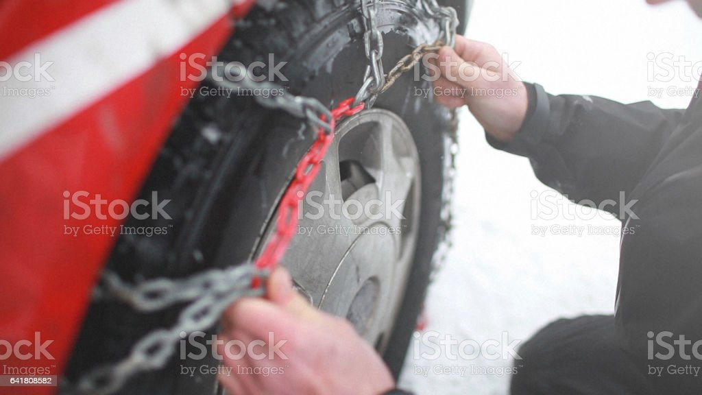 Man putting car chain on wheel stock photo