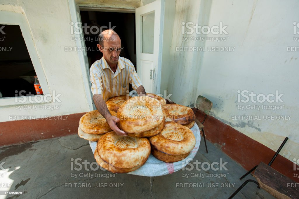 Man putting central asia style bread on tray stock photo