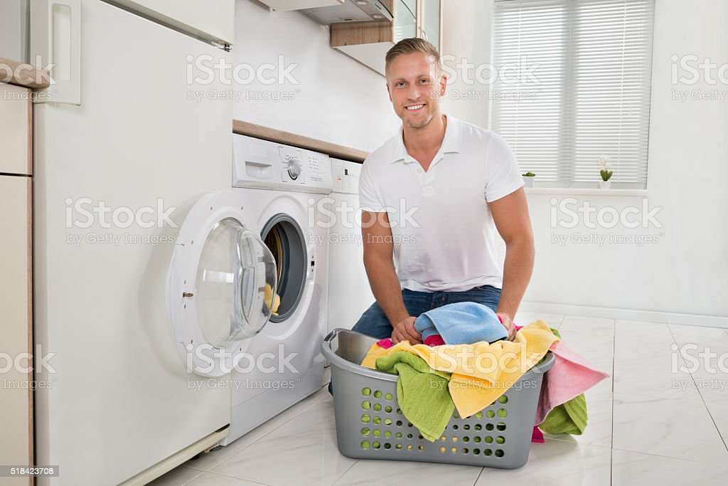 Man Putting Colorful Towels Into The Washing Machine stock photo