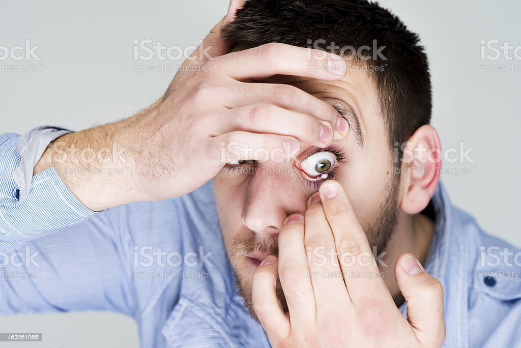 Man putting contact lens in his eye royalty-free stock photo