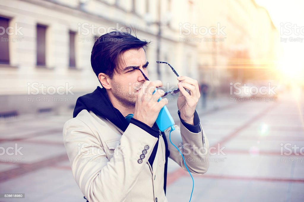 Man putting eyeglasses outside stock photo