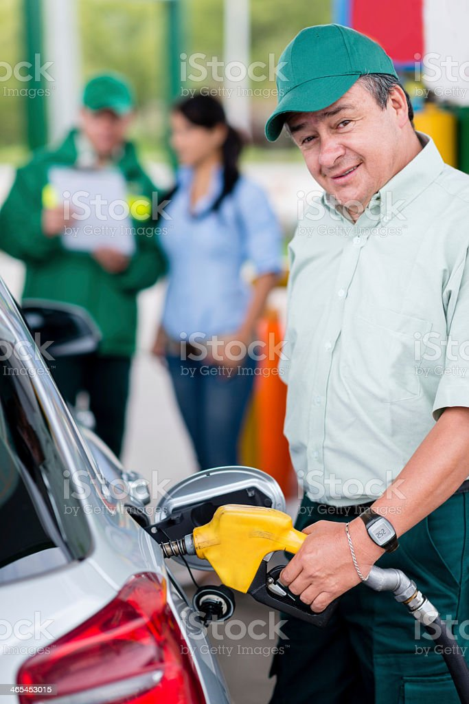 Man putting fuel in the car stock photo