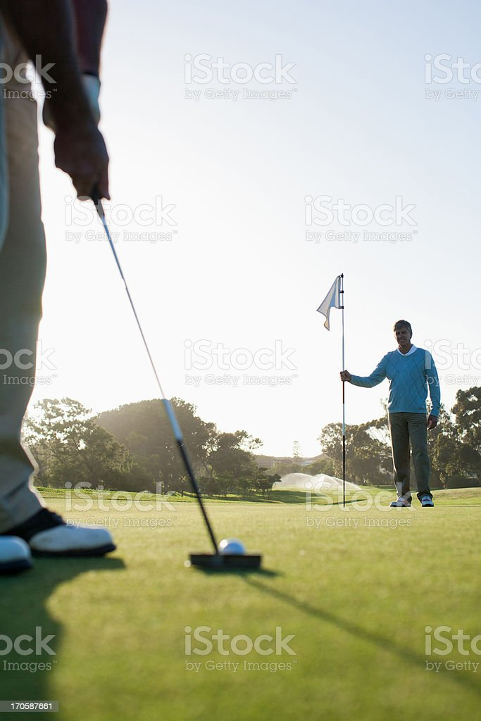 Man putting golf ball royalty-free stock photo