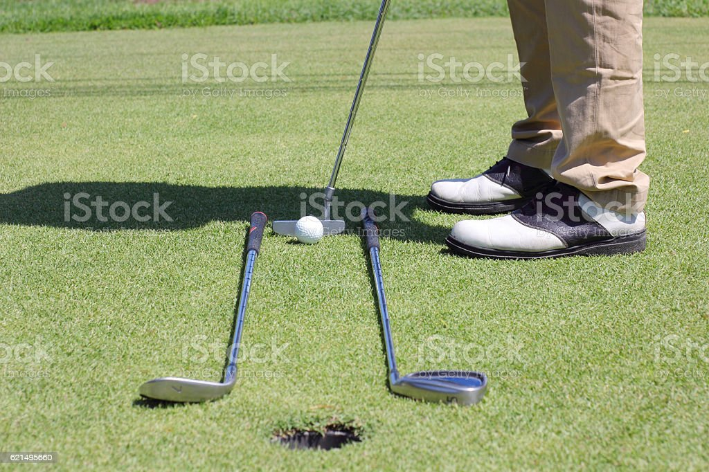 Man putting golf ball with hole. stock photo
