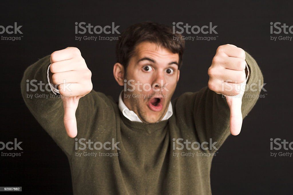 A man putting his thumbs down in a disapproving manner stock photo