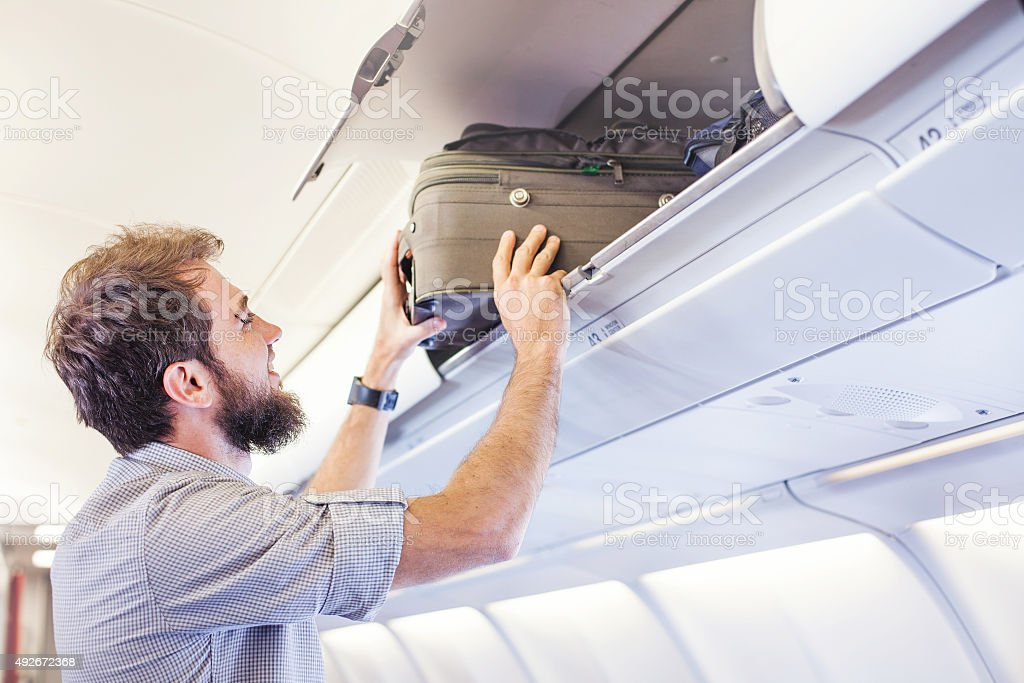 man putting luggage on the top shelf on airplane stock photo