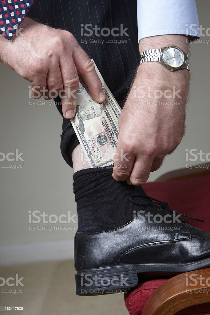 Man putting money in sock royalty-free stock photo