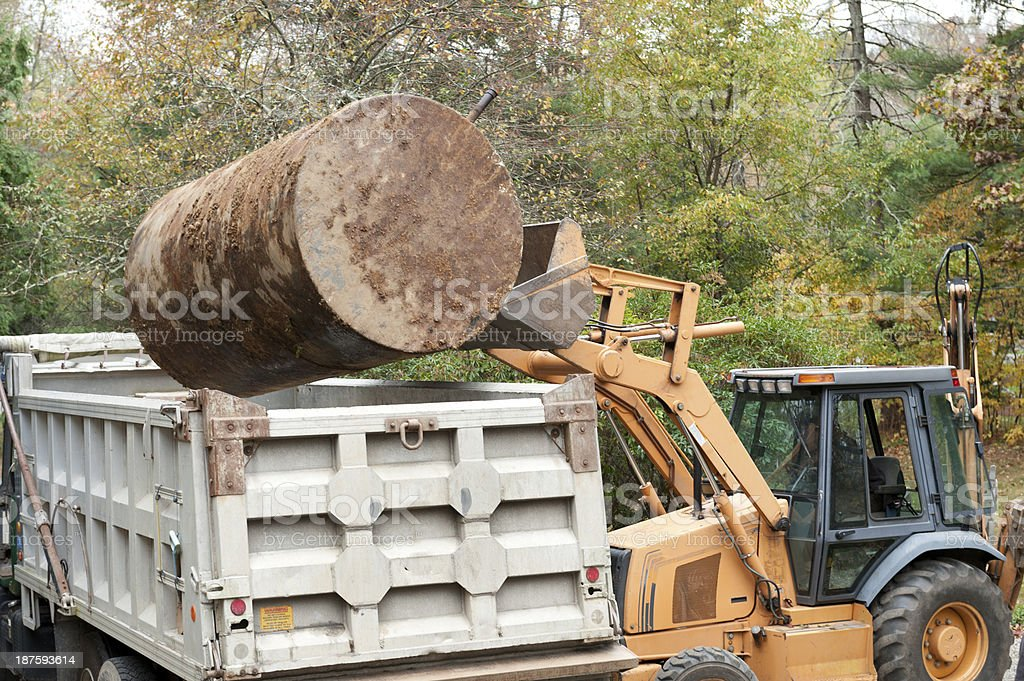 Man putting old underground oil tank into dump truck stock photo