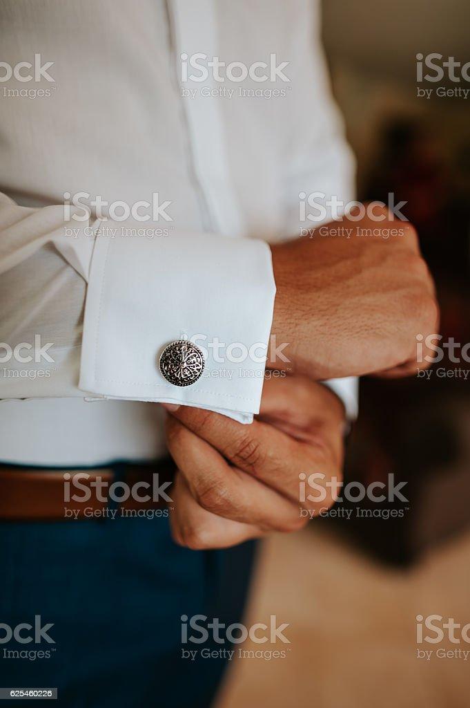 Man putting on cuff-links stock photo