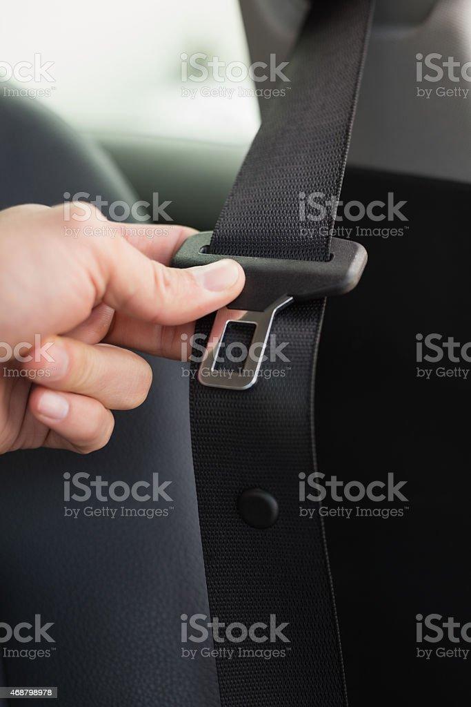 Man putting on his seat belt stock photo