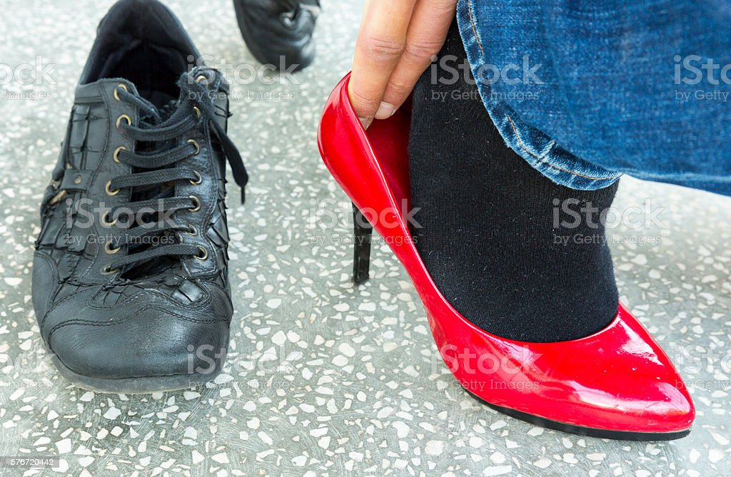 Man putting on red ladies shoes stock photo