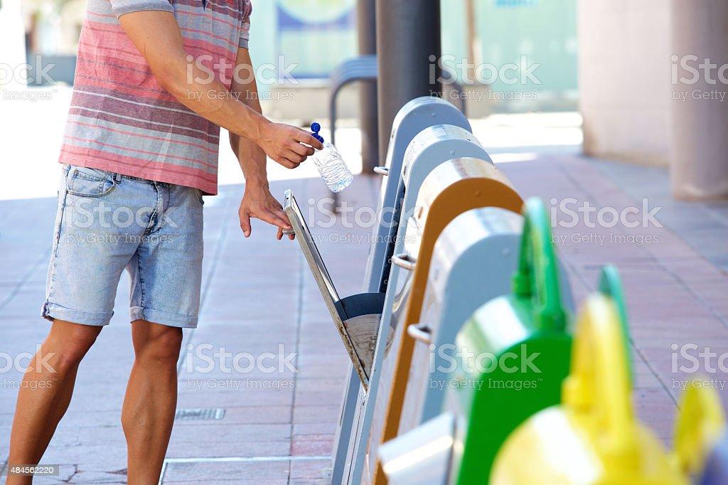 Man putting plastic bottle in recycling bin stock photo