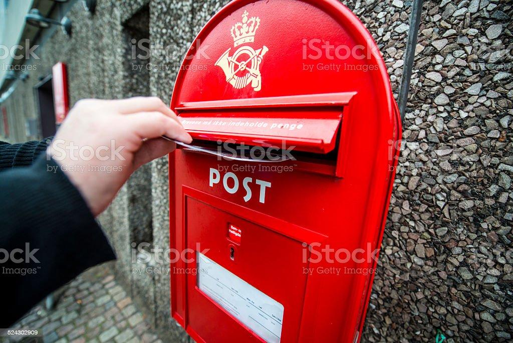 Man putting postcard into mailbox on the street, Copenhagen stock photo