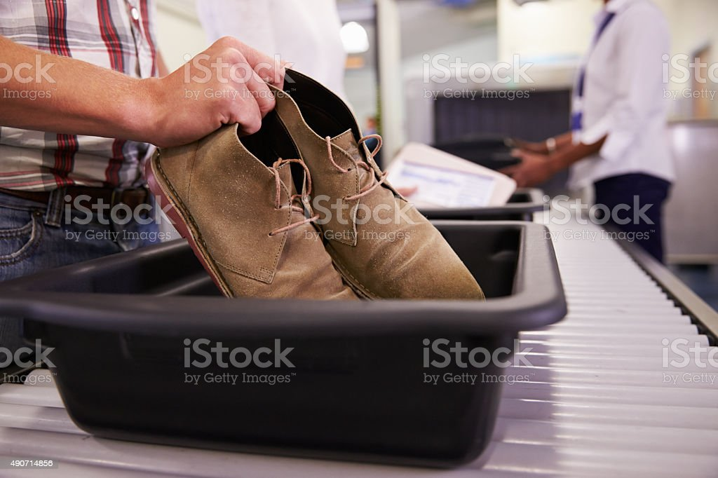 Man Putting Shoes Into Tray For Airport Security Check stock photo