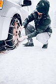 Man Putting Snow Tire Chains On Car