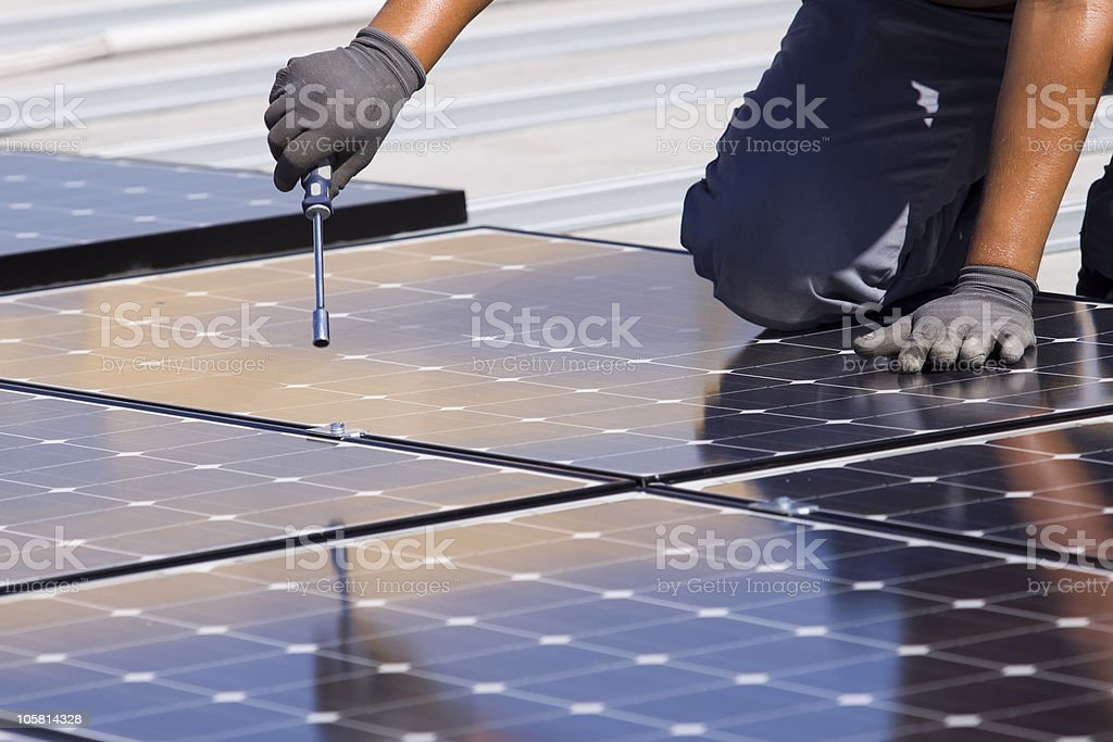 Man putting together solar panels stock photo