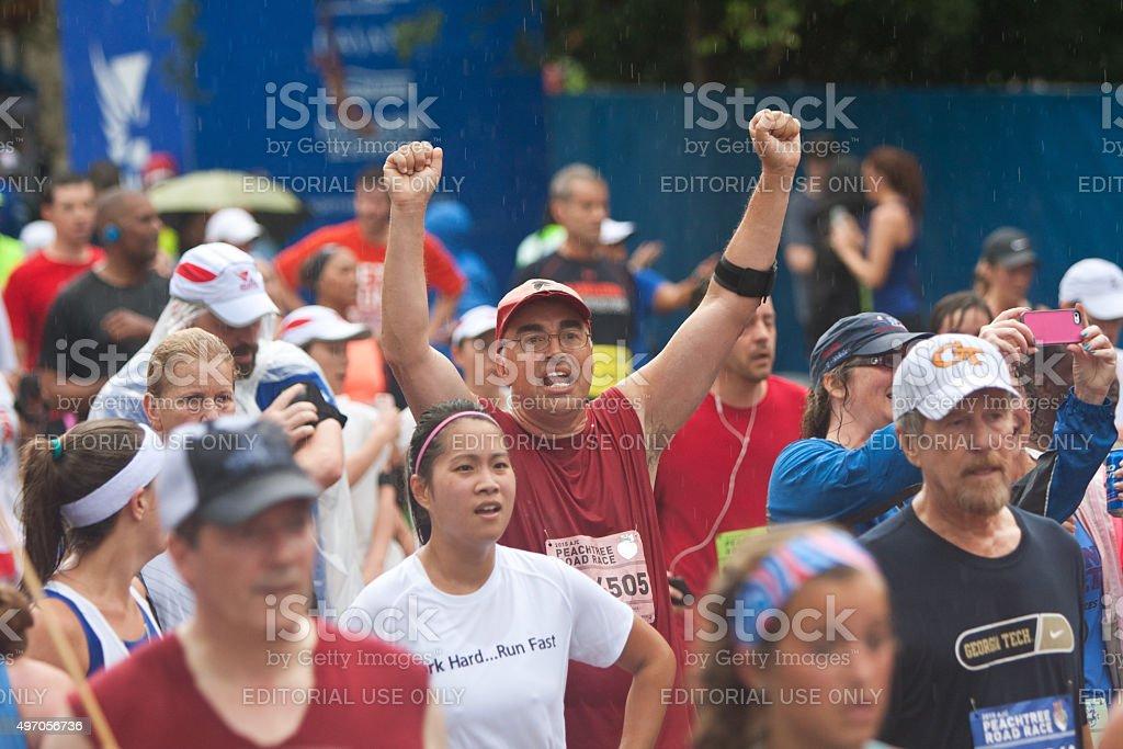 Man Raises Arms Triumphantly Finishing Atlanta 10K Road Race stock photo
