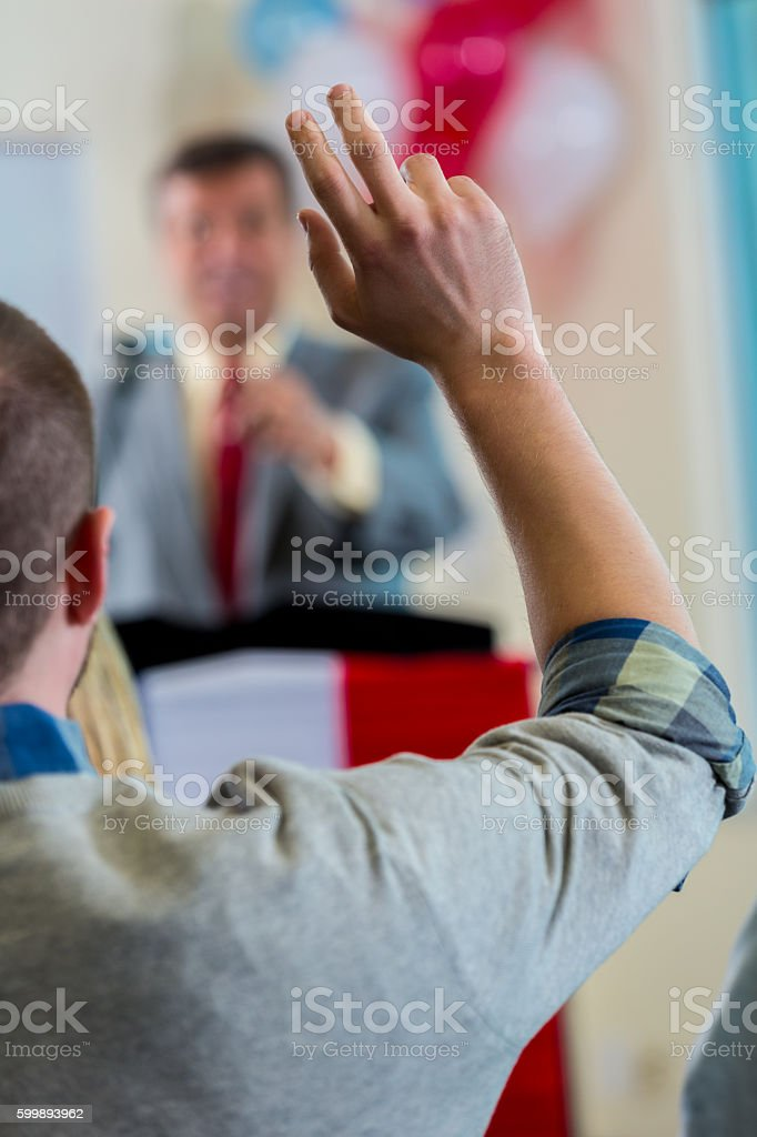 Man raising hand during political town hall meeting stock photo