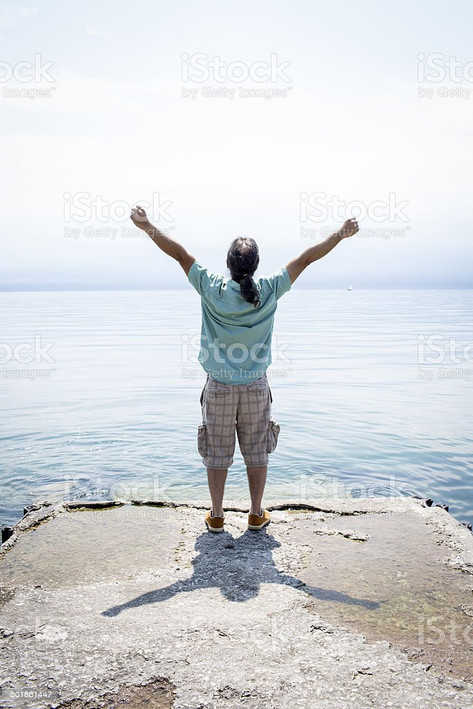 Man raising his arms at the end of a jetty royalty-free stock photo