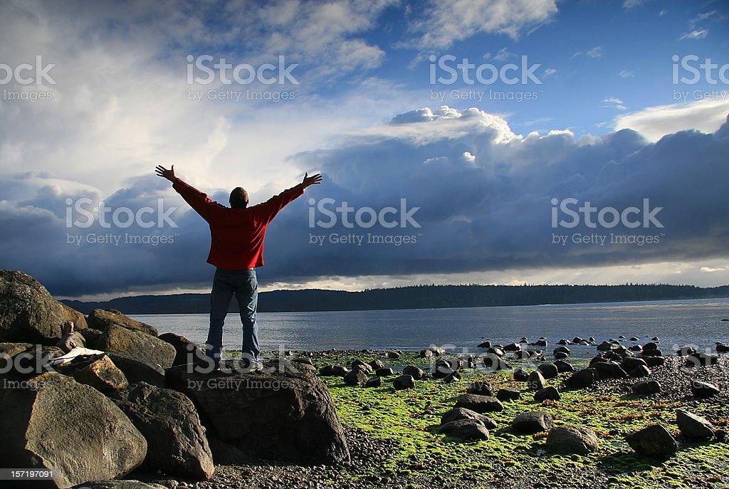 Man Raising His Hands to Heaven in Beautiful Ocean Setting stock photo