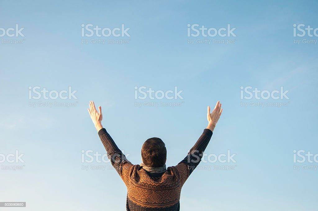Man Raising His Hands to Sky stock photo