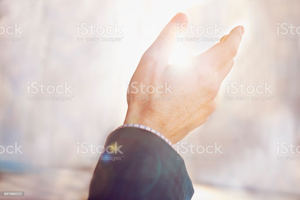 Man raising praising hand gesture against multicolored background stock photo