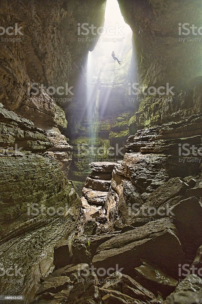 Man Rappels into cave stock photo