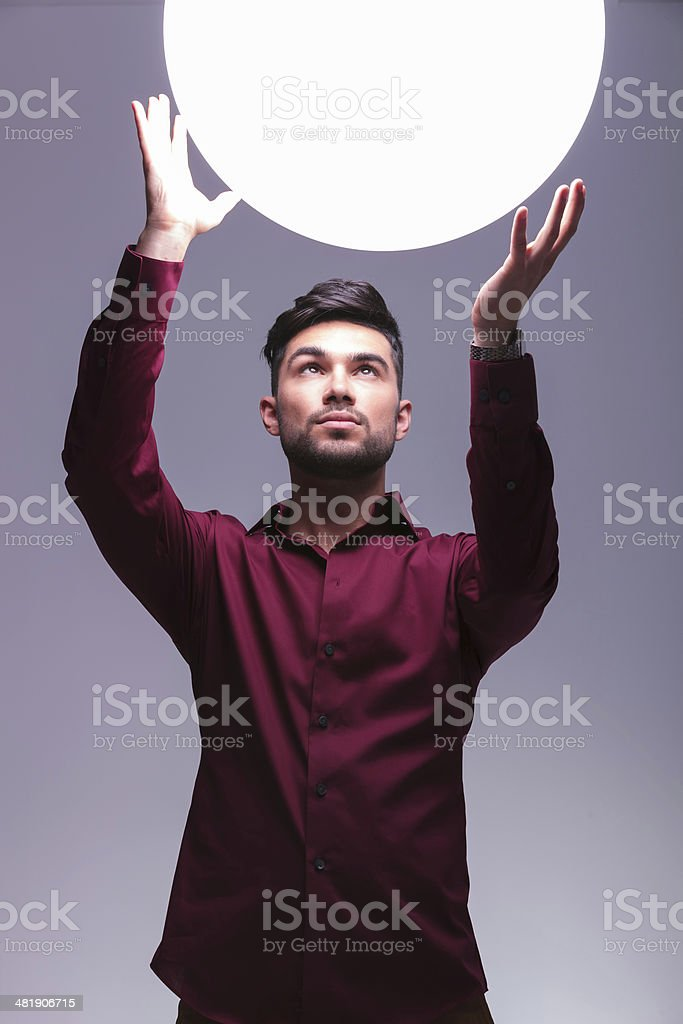 man reaching out to a big ball of light royalty-free stock photo
