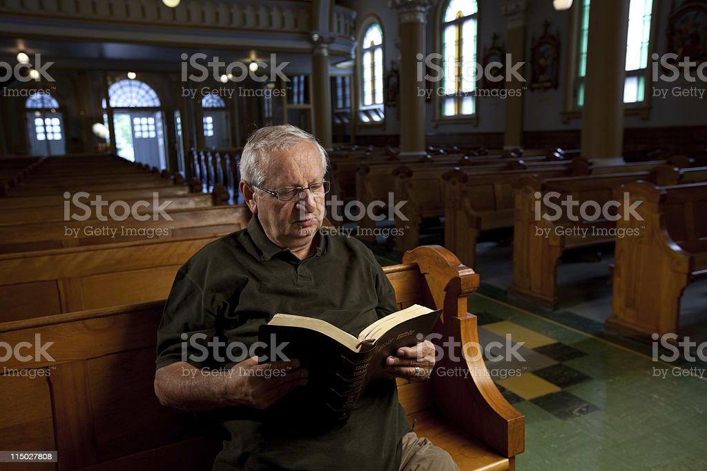 Man reading a bible in church royalty-free stock photo