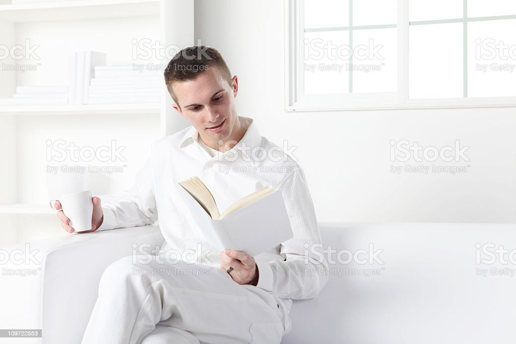 Man reading a book and drinking coffee royalty-free stock photo