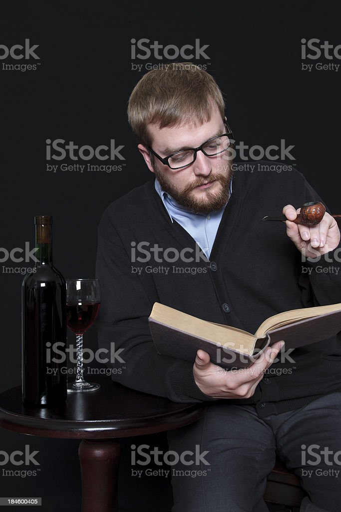 Man Reading a Book and Enjoying Pipe stock photo