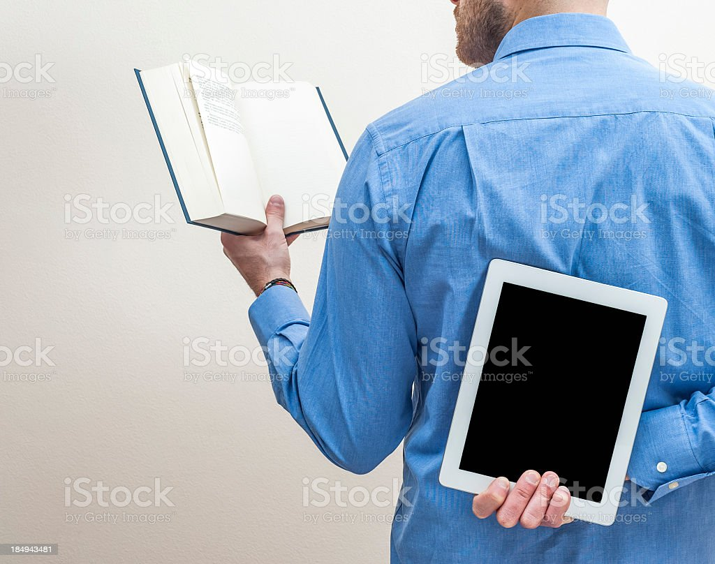 Man Reading A Book And Hiding Digital Tablet stock photo
