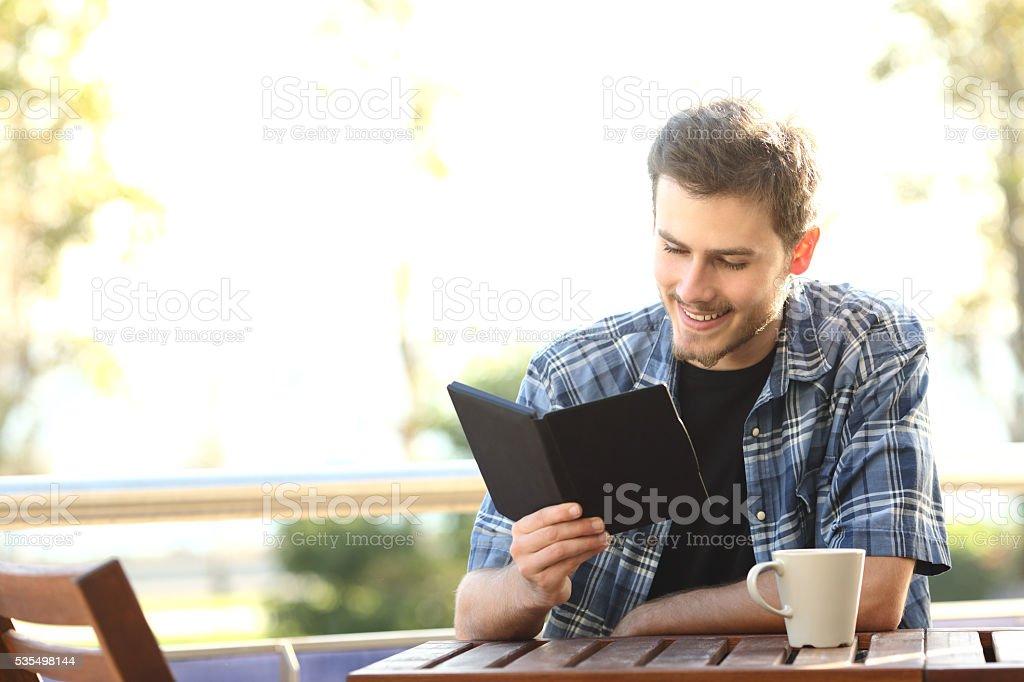 Man reading a book in an ebook reader stock photo
