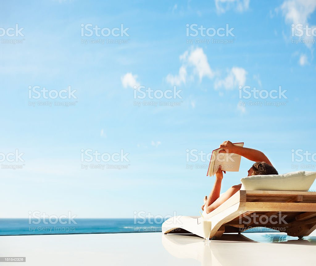 Man reading a book while lying on deckchair royalty-free stock photo
