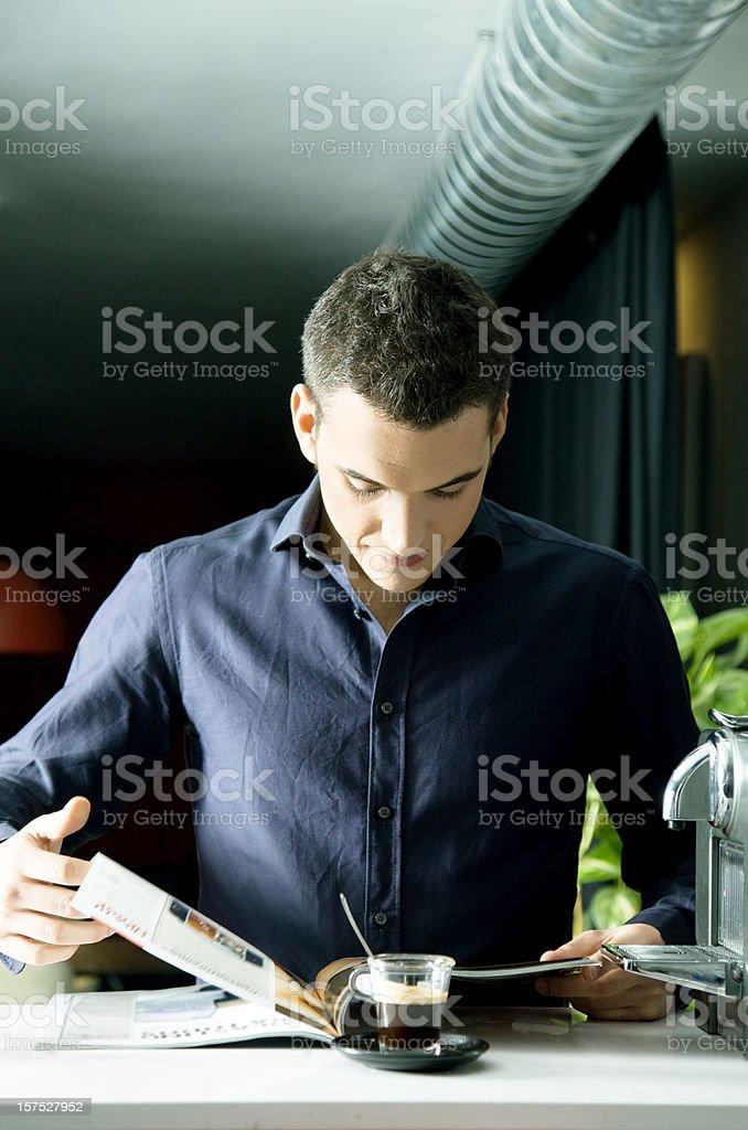 Man reading a magazine while having coffee royalty-free stock photo