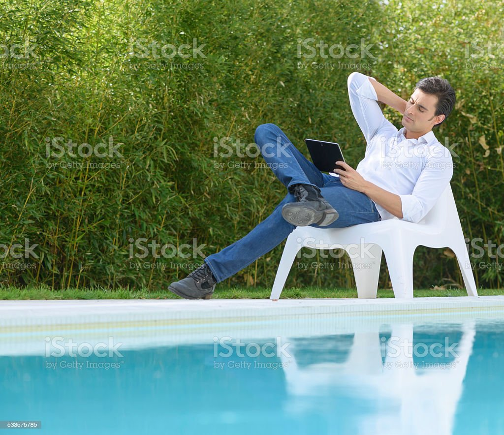 Man reading a tablet by the pool stock photo