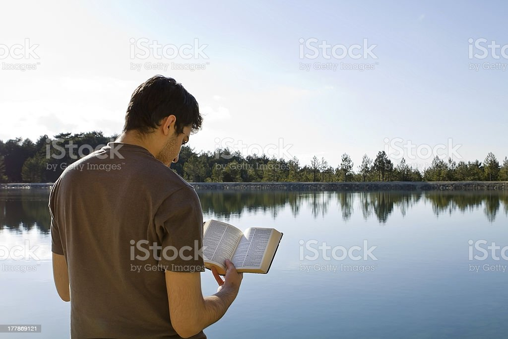 Man Reading Bible By Lake stock photo